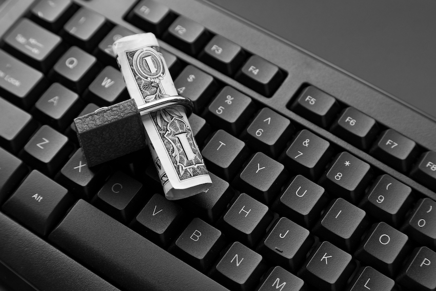 High Angle Shot Of A Lock Around A Dollar Bill On A Black Laptop