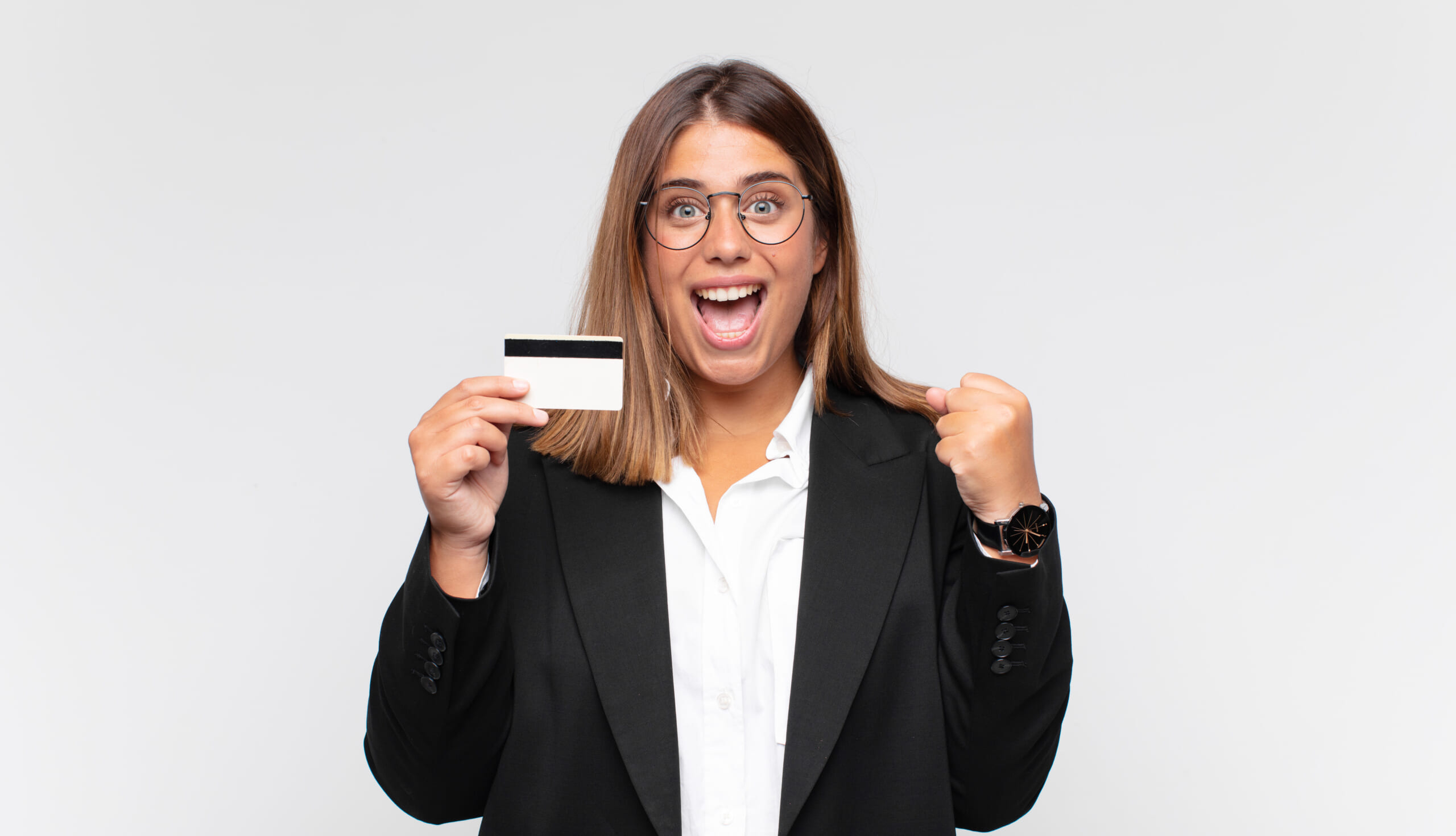 Young-woman-with-a-credit-card-feeling-shocked-excited-and-happy-laughing-and-celebrating-success-saying-wow.jpg