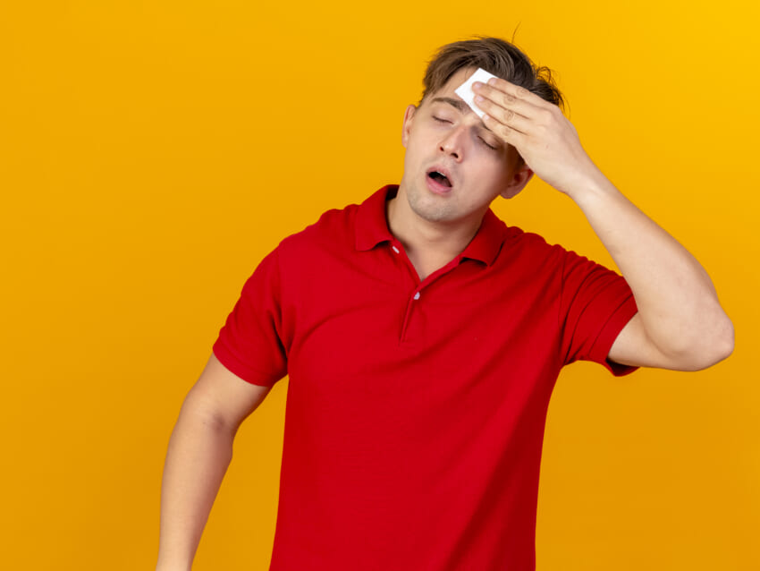 Weak-young-handsome-blonde-ill-man-wiping-sweat-with-closed-eyes-isolated-on-orange-background.jpg